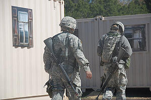 Two soldiers train in a shipping container based MOUT.