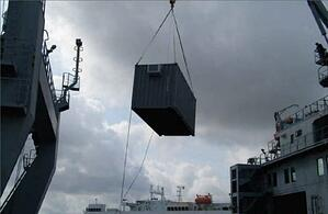 temporary workforce housing container being transported by crane.