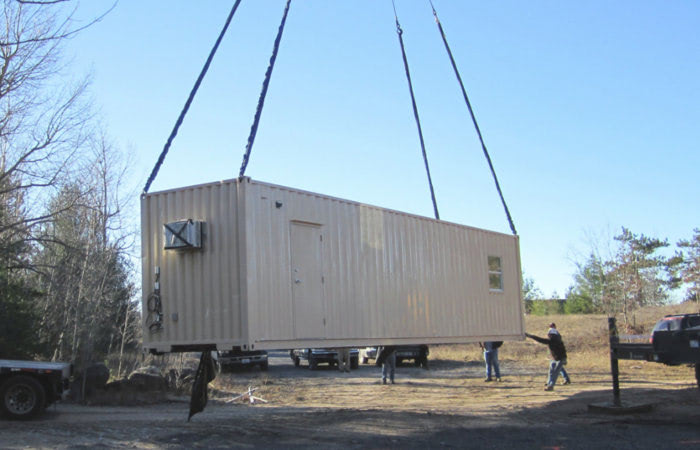 Portable conex container cabin being placed at a remote location without a foundation.