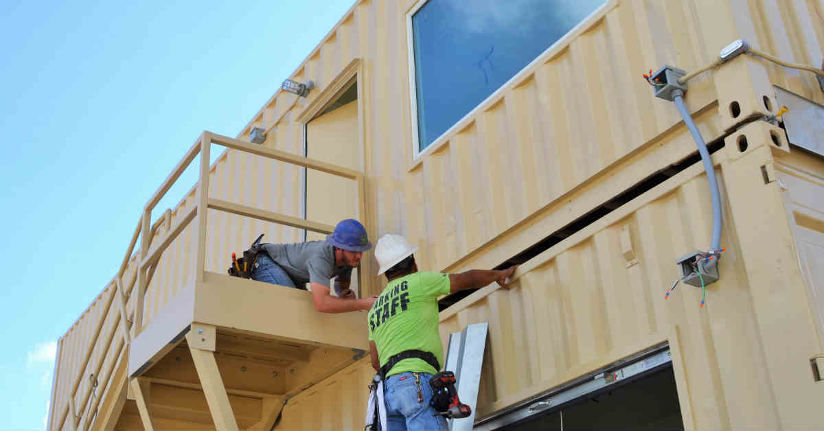 Two Falcon employees perform a quality control check on a shipping container building.