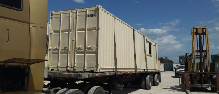 Shipping container module loaded on truck for modular construction.