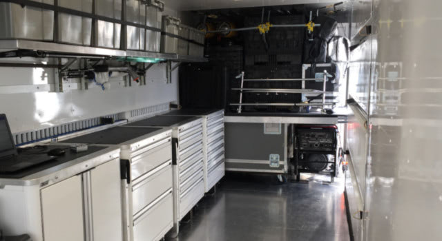 Interior of mobile conex container converted into garage space with storage.