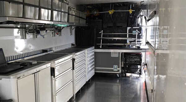 Interior of shipping container modified into a mobile car garage.