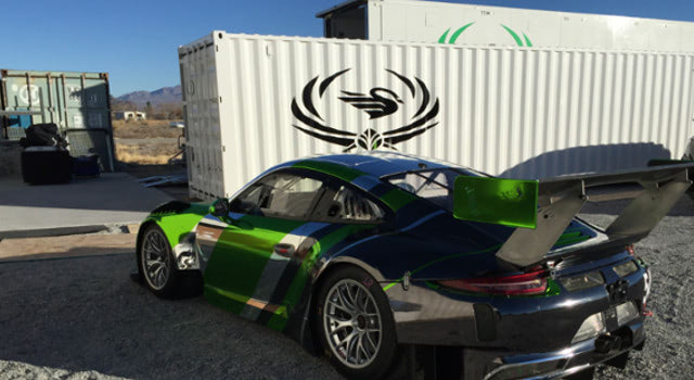 Black Swan Racing's porsche 911 in front of their custom mobile car garage.