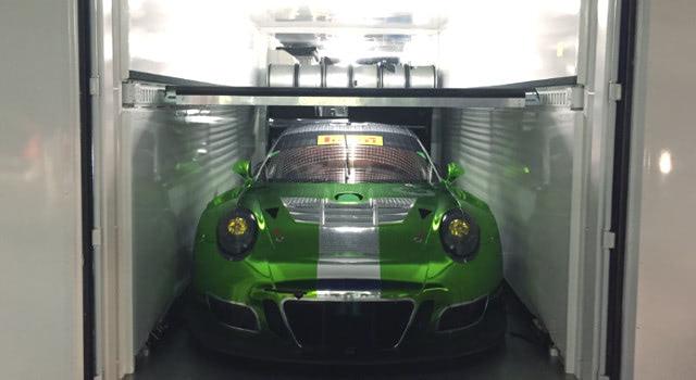 Porsche 911 inside mobile car garage made from conex container