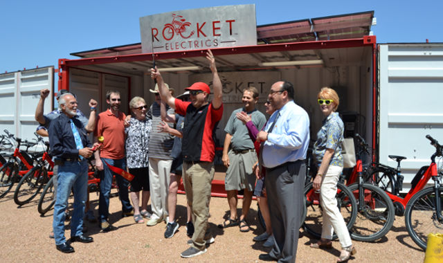 Rocket Electrics and its supporters cheer after cutting the ribbon to their store front location.