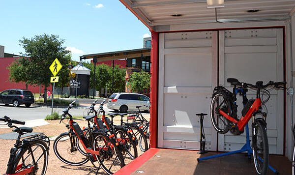 Interior of container-based store front which doubles as secure storage for e-bike fleet.