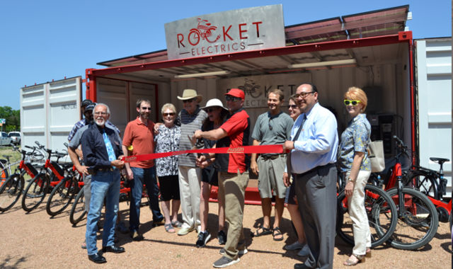 John Dawson, Nicole Zinn, and members of the Austin Chamber of Commerce cut ribbon on new store front.