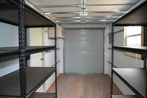 Conex storage container with shelving and roll up door.