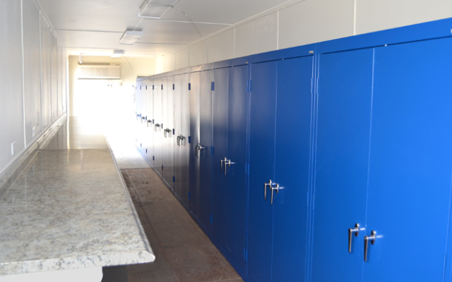 Interior or onsite storage container with work surface and cabinets.