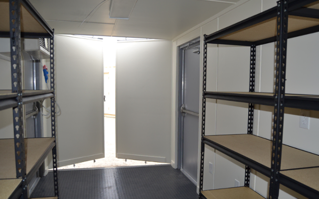 Interior of onsite ISO storage container with shelving.