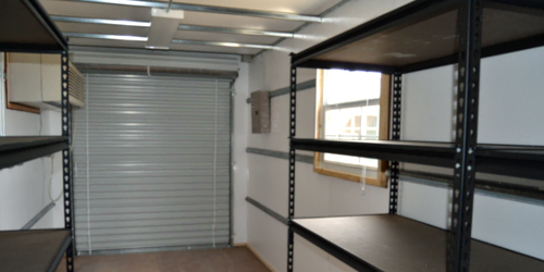 Interior of shipping container modified into a storage unit with an overhead door and