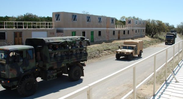 Trucks drive through conex container-based training village.