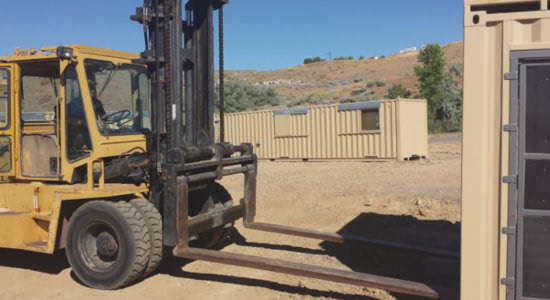 A forklift quickly assembles a conex container training facility for police and firefighters.