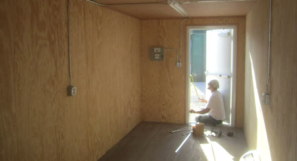 Interior of a conex container workshop with plywood paneling