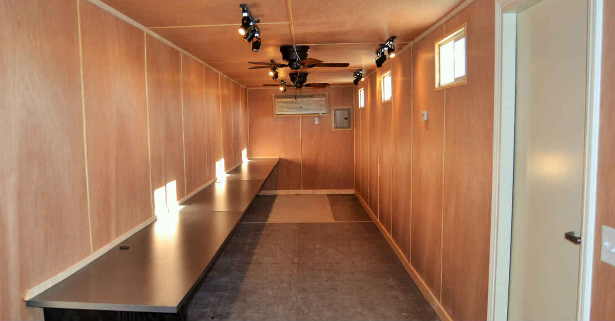 Interior of a portable sales office finished with wood paneling and desks.