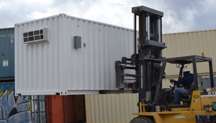 Mobile shipping container field office being transported by forklift.