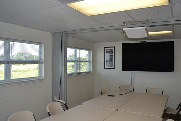 A container-based conference room finished out with drywall.