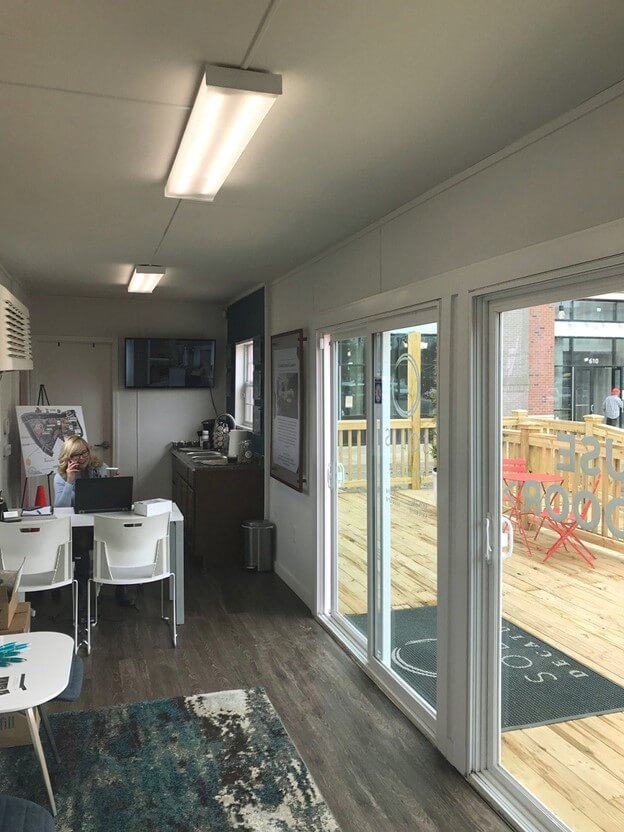 Interior of a shipping container office with sanded wood panel walls.