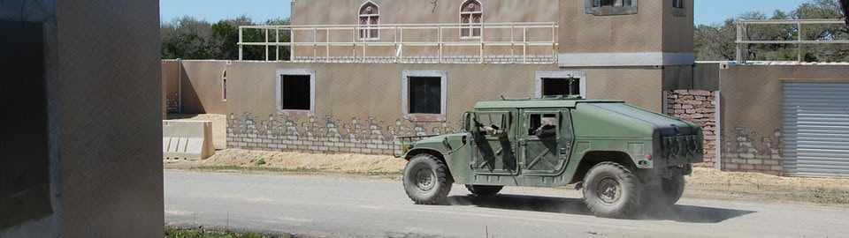 Military vehicle driving through shipping container based MOUT training facility.