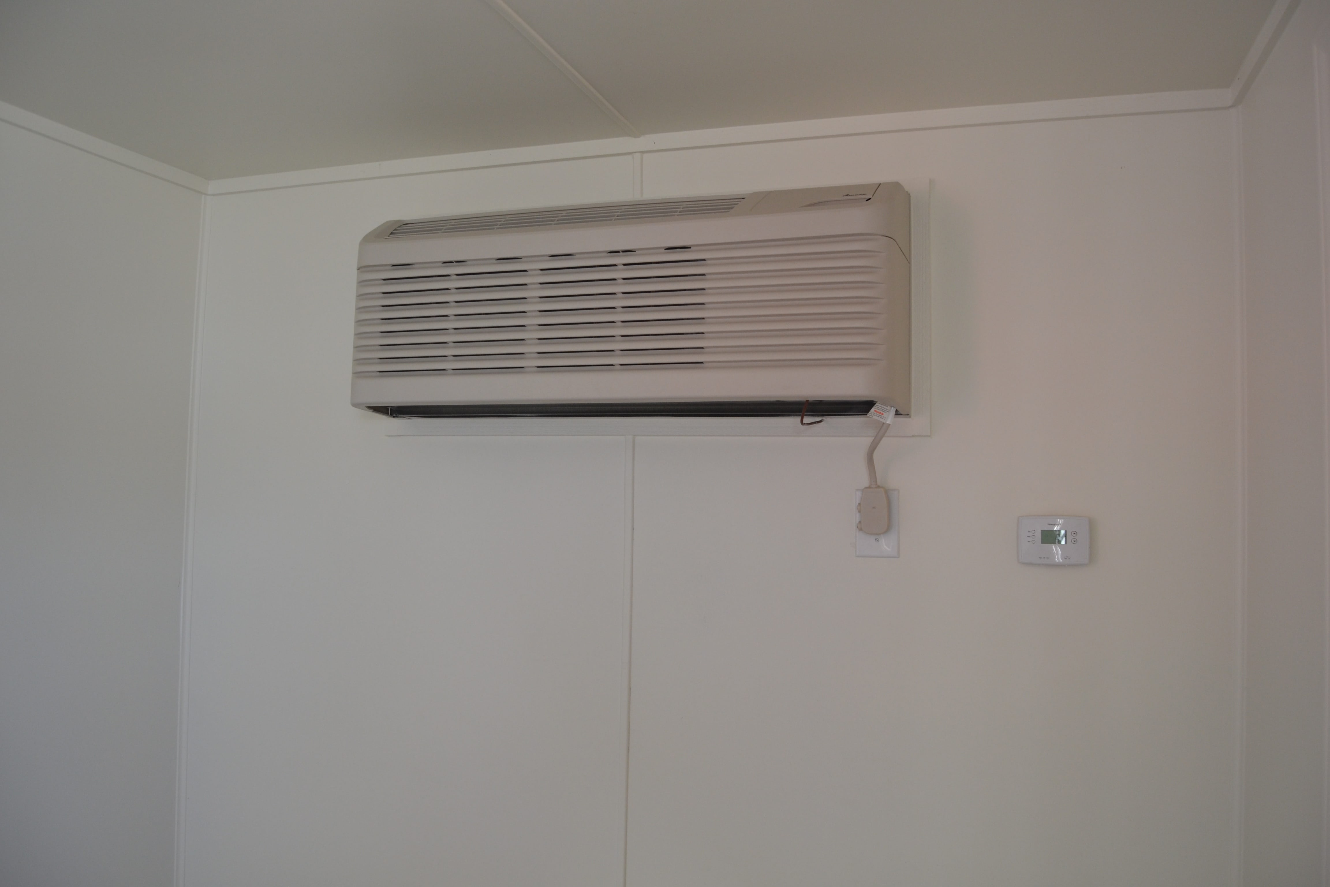 Air conditioning (HVAC) unit installed in wall of mobile container office.