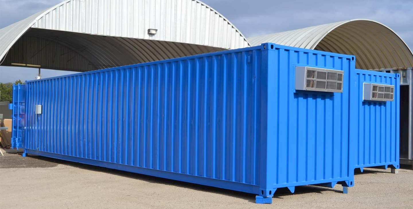 blue-shipping-containers-in-front-of-hangers