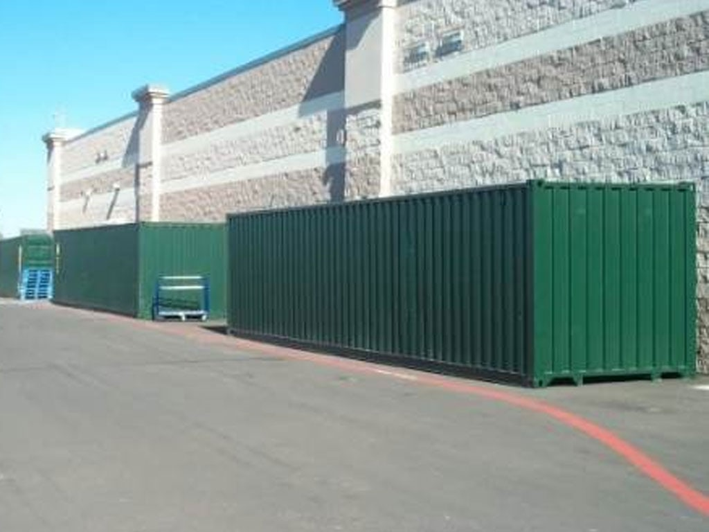 Storage containers next to building in parking lot