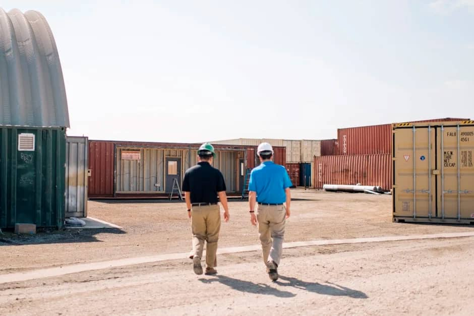 an architect and engineer walk between shipping container structures