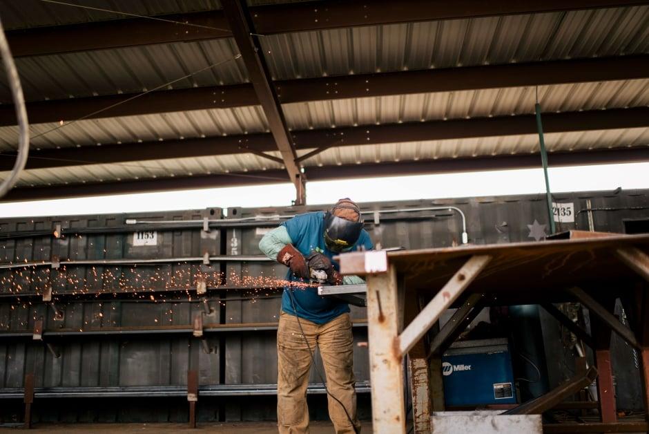 construction site worker grinding metal