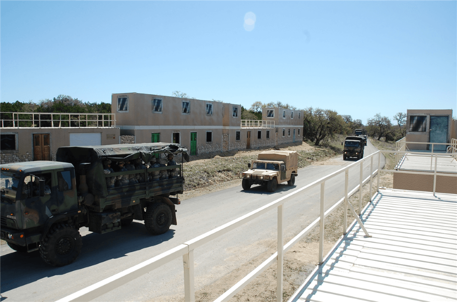 shipping container military training village MOUT with military vehicles driving on the road