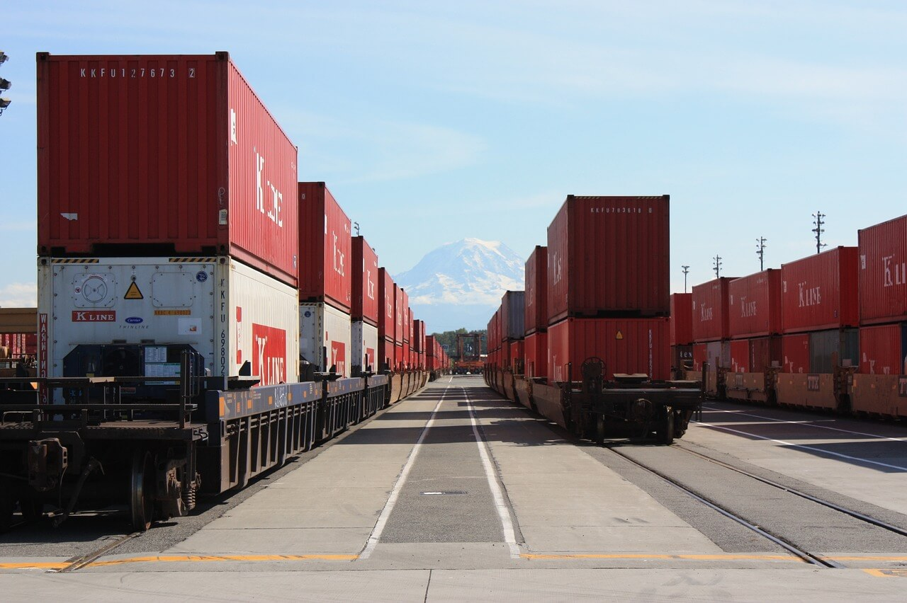 shipping containers on multiple trains with mountain in the back