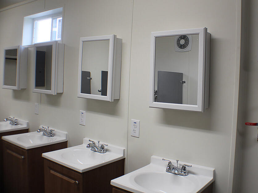 four sinks and mirrors in a shipping container bathroom