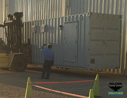 A forklift places a restroom building on site.