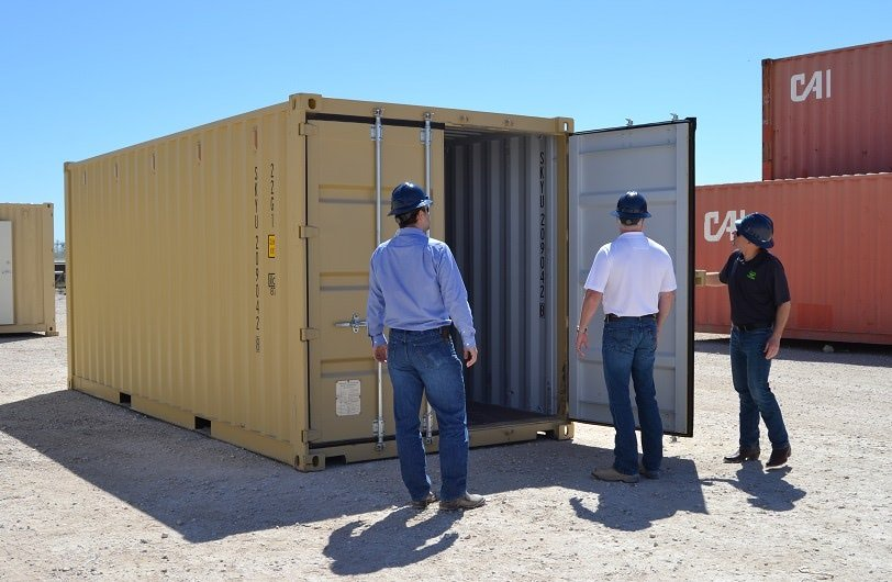A Falcon Structures Salesmen shows customers how to open a container door.