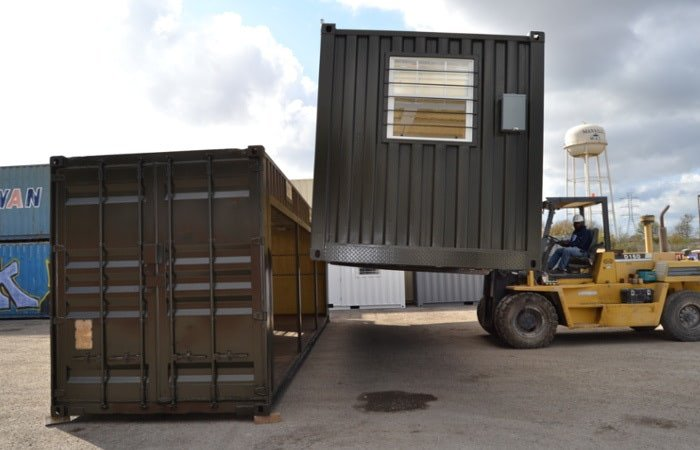 Forklift placing shipping containers together to create a structure