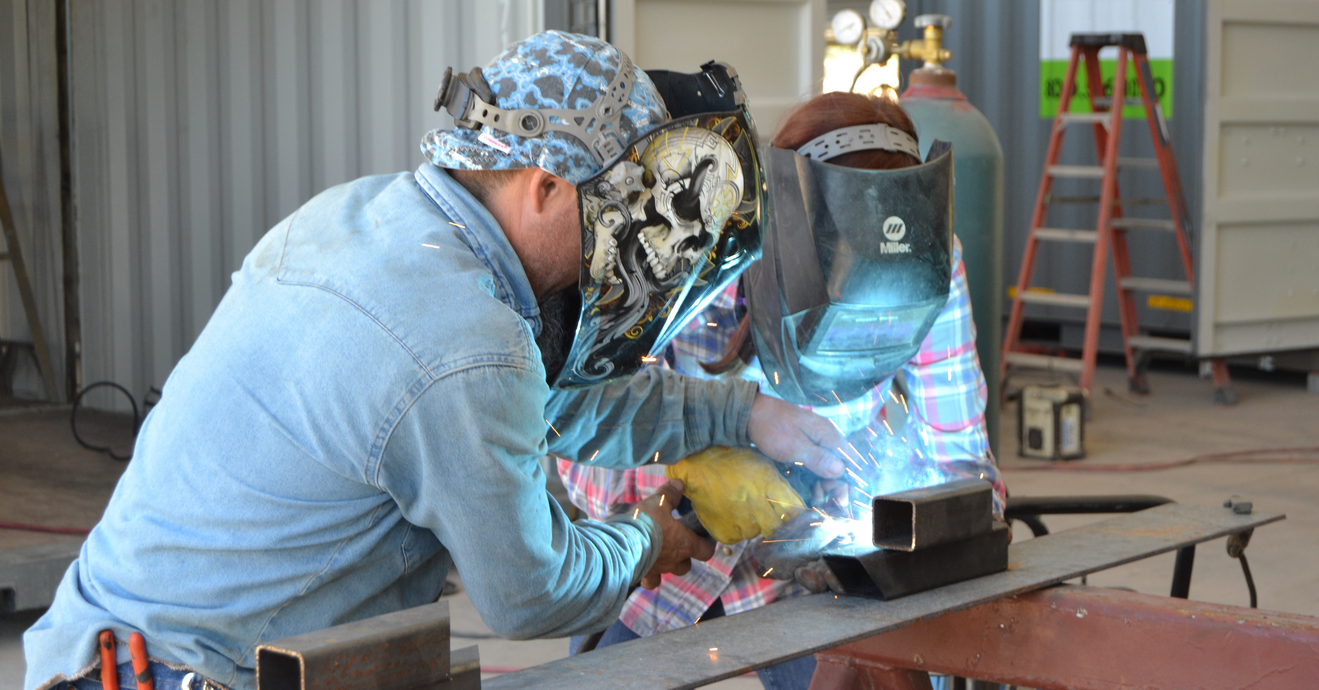 Adrian helps new boxpert, Paige, learn the basics of welding.