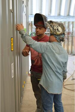 Welders plan how they will cut a shipping container with a plasma cutter